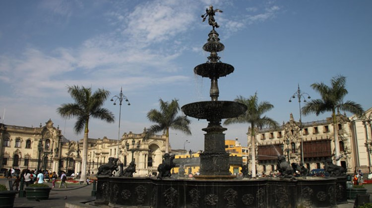 The fountain at the center of Lima's Plaza Mayor, with the Presidential Palace in the background at left and the Archbishop's Palace at right.