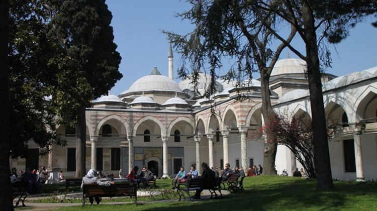 Visitors relax in a courtyard of the former Ottoman sultans' residence, Topkapi Palace. The Pavilion of the Holy Mantle in the background houses relics linked to the Prophet Mohammed and other religious relics.