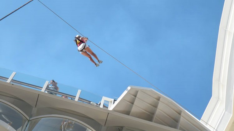 One of the first users to experience the Zip Line ride on the Oasis of the Seas, as seen from the Boardwalk.