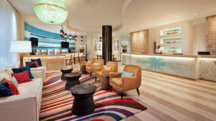 The Best Western Premier, the first full-service, Haitian-owned, U.S.-branded hotel to open in Haiti serves as a showcase for the country's art. The hotel's lobby offers a modern, welcoming reception area with spacious seating and a bar area.