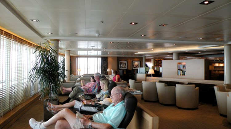 Passengers reading in Seabourn Square during a day at sea.