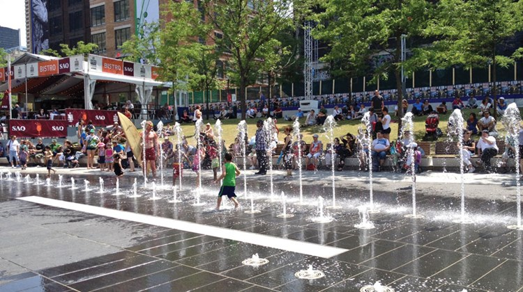 During the warm weather, kids splashed in street fountains that spouted geysers of water. TW photo by Gay Nagle Myers