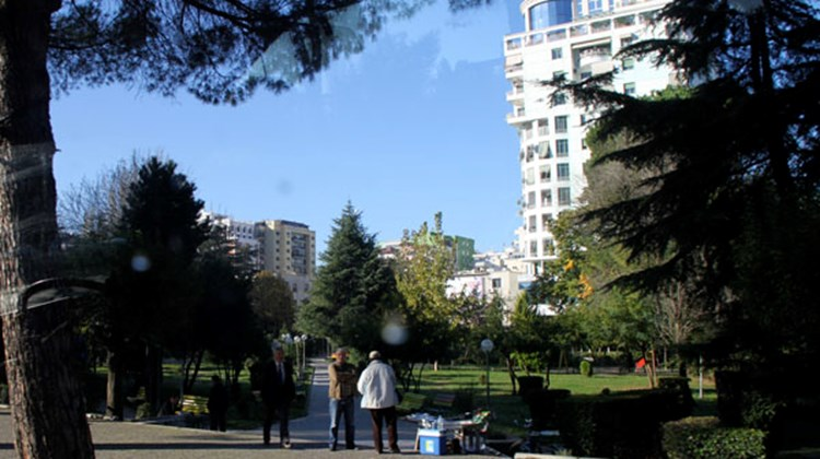 A high-rise building sits well back from a central city boulevard, with a tranquil park in the foreground.