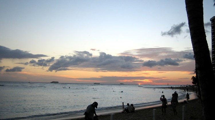 Sunset on Waikiki Beach is a special time of the day: People gather on the sand to watch the sun dip below the waterline.