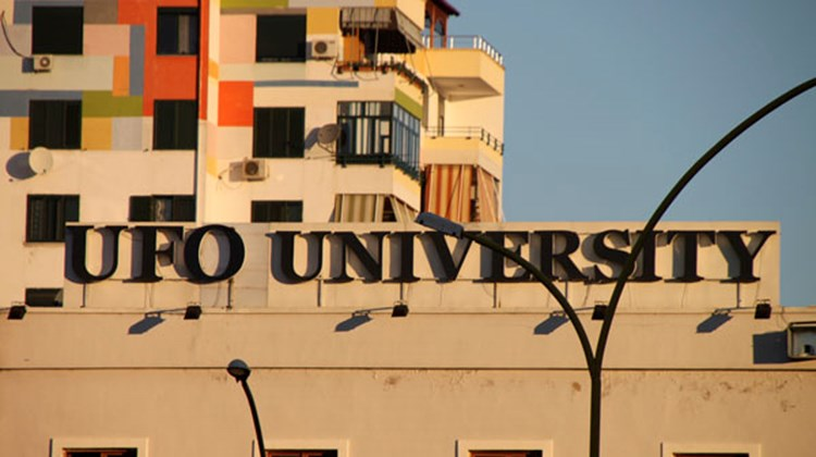 Signage for a Tirana university (UFO stands for Universitas Fabrefacta Optime), with apartment buildings in the background.