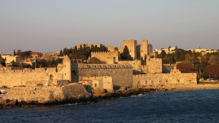 An early morning view of the 14th century walls -- built by crusading knights -- that surround Rhodes, the capital city of the island of Rhodes. The Palace of the Grand Masters is visible slightly to the right of center.
