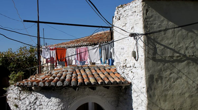 In Kruja, tile-roofed, white plaster houses with their signs of life: laundry on the line and a chaos of electrical wires.