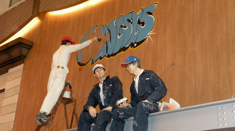 One of the pieces of art in the ship's Royal Promenade is three statues of workers on the Oasis -- and one is cleaning up a sign that says Genesis, the name of the Oasis project.
