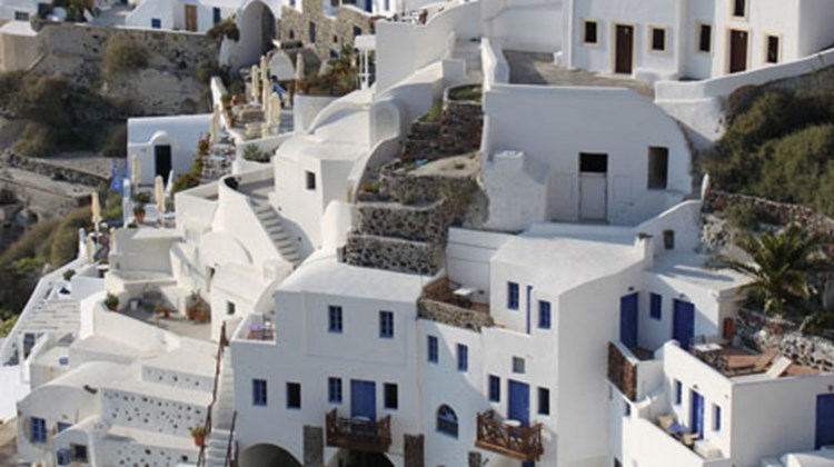The iconic view of houses cascading down the side of a Santorini cliff in Oia, a small village at the tip of the crescent-shaped island.