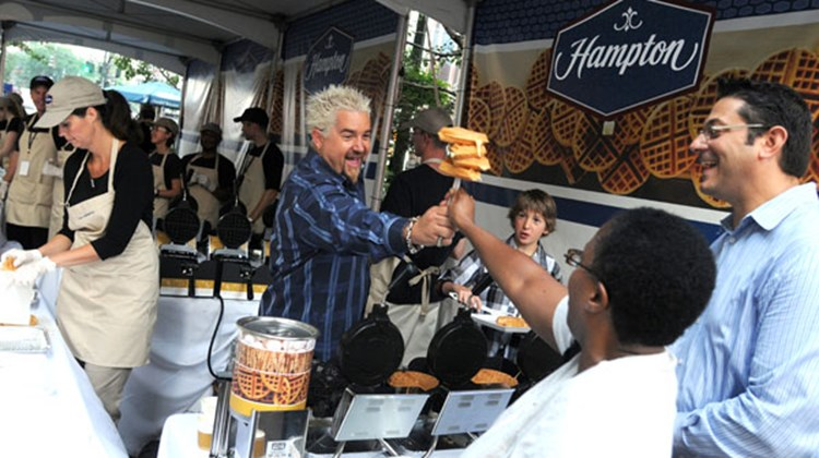 Chef and TV celebrity Guy Fieri helped to kick off Hampton Hotels' new breakfast program in New York's Herald Square Park on June 17. Here, Fieri serves waffles to New York residents Patricia Dyett and Jay Silva.