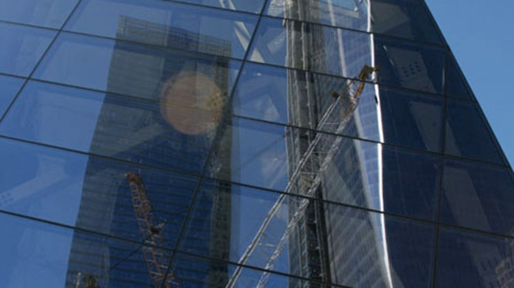 A reflection of 1 WTC in the 9/11 Memorial Museum, which sits at the center of the plaza.