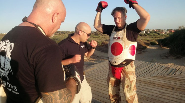Krav maga instructor Shai Fargian (in glasses) teaches Travel Weekly Destinations Editor Kenneth Kiesnoski and his brother Jeffrey how to take a punch
