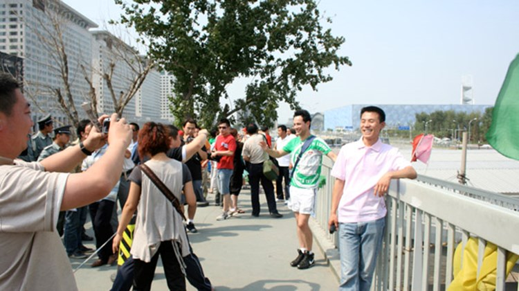 Visitors posing in front of the Beijing Olympics National Stadium and National Aquatics Center.