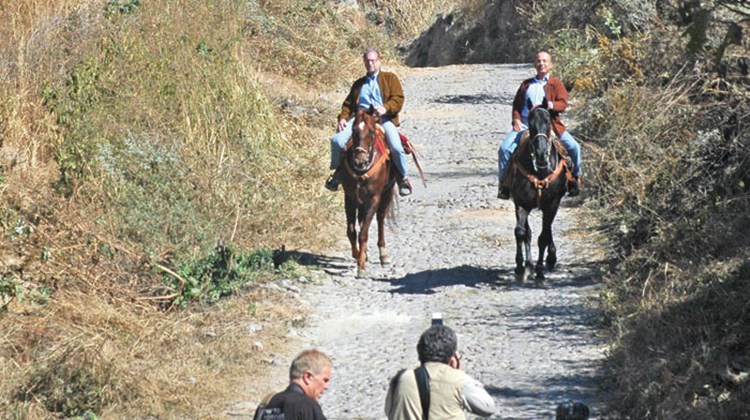 "Travel Weekly's editor in chief, Arnie Weissmann, accompanies a TV film crew on President Felipe Calderon's personal tour of his country. Pictured here, CBS News travel editor Peter Greenberg and Mexico's president, Felipe Calderon, explore the Jose Cuervo estate in Tequila on horseback during the filming of the PBS special ""Mexico: The Royal Tour."" TW photo by Arnie Weissmann"