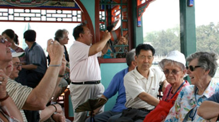 Traveling by tour boat, a group of American tourists views the Summer Palace outside of Beijing.