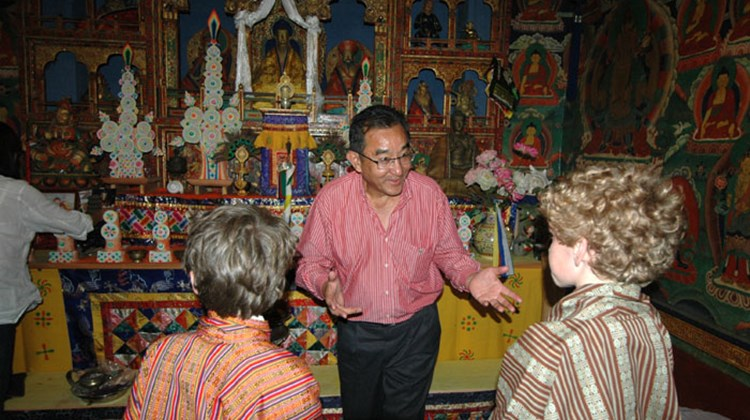 Dasho Tobgye Dorji explains the meaning of items in the shrine room of Hotel Gangtey Palace to the author's sons
