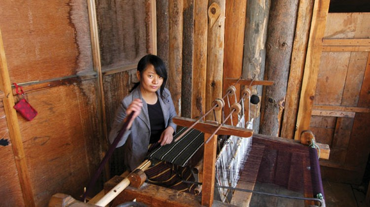 A woman weaves traditional designs at the Yatha Weaving Center near Bumthang