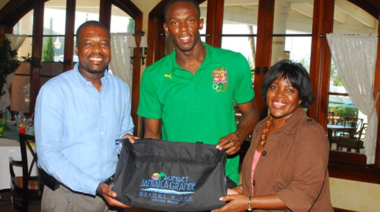 Clifton Reader, GM of Sunset Jamaica Grande Resort & Spa (left) Charmaine Deane, the hotel's dir. of corporate communications (right) welcome Usain Bolt to the property.