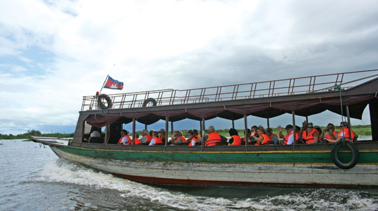 Ama Waterways passengers ride motorboats across Tonle Sap Lake to board the AmaLotus for the inaugural downstream sailing