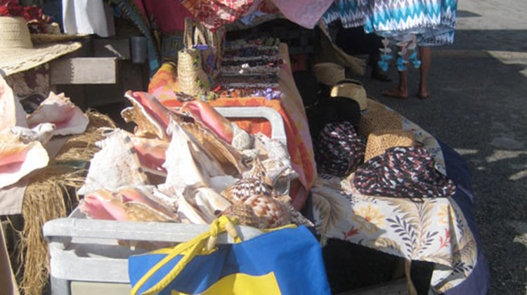Vendors' stalls display fabrics, bags, straw baskets and jewelry at the open-air markets on GBI