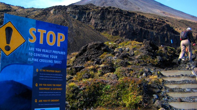 Hikers pass a warning sign aimed at deterring the unprepared at the base of the Tongariro Alpine Crossing's first real climb. Travelers interested in tackling the trail with an expert guide can book a day with Adrift Outdoor Guided Adventures, a company that provides everything from warm clothing, waterproof gear, hiking boots and a picnic lunch along with all sorts of geologic, cultural, botanical and birding insight.