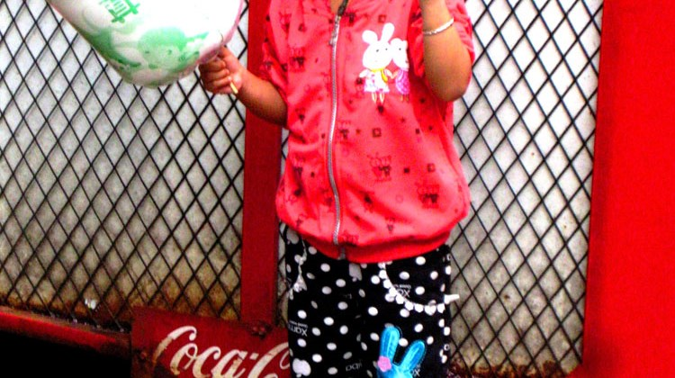 A young girl poses with cotton candy in front of a rusting Coca Cola machine on Beijing Road.