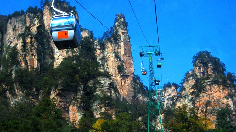 Visitors begin their trip up to the Yuanjiajie Scenic Area's viewing locations, connected by a series of paved hiking pathways and brief bus rides, onboard a relatively short but photogenic cable car ride up to Tianzi Mountain.