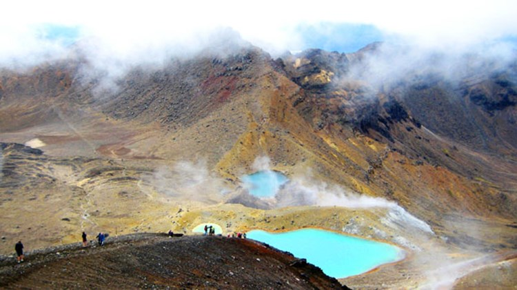 Hikers photograph Tongariro's Emerald Lakes, which are also acidic with a PH level of around 3.5 and owe their bright color to minerals like sulfur that leach into the fresh water from nearby geothermal vents.