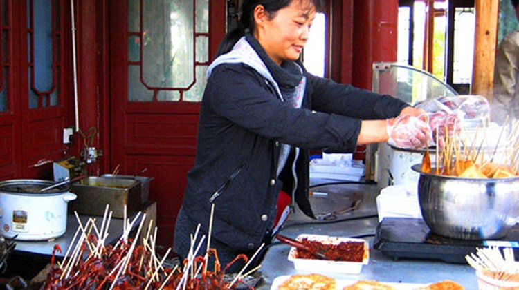 Visitors can purchase a marinated, fried swallow on a stick, a popular Zhangjiajie delicacy, at this vendor's location in the Yuanjiajie Scenic Area.