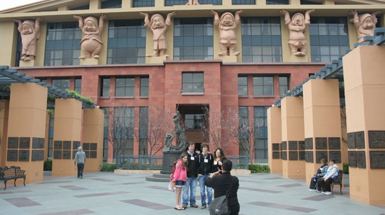 "Taking an official tour of one's native stomping grounds is bound to be enlightening. When that home turf happens to be the adopted town of Walt Disney, and the tour is hosted by Adventures by Disney (ABD), things could have gone several ways. Pictured here, a family on the ABD tour poses in front of the Michael D. Eisner building, aka ""the Seven Dwarfs building,"" at Walt Disney Studios. Photos by Michelle Baran; posted March 8, 2012"