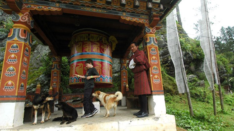 Mr. Nado watches as the author's 8-year-old sun spins a prayer wheel near the ruins of Drukgyal Dzong.