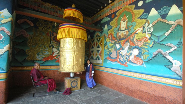 A woman turns a wheel covered in gold leaf at the entrance of Trongsa Dzong.