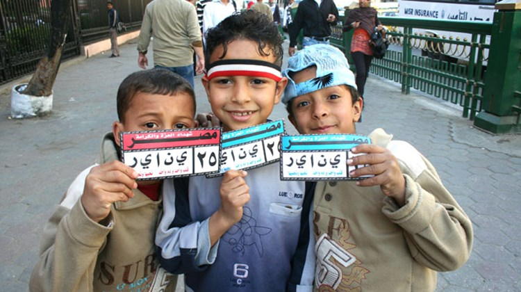 "Egyptian kids outside the Egyptian Museum in Cairo show off their ""January 25"" bumper stickers and an Egyptian flag headband."