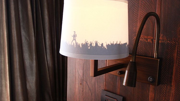 An audience in silhouette on a nightstand lampshade.