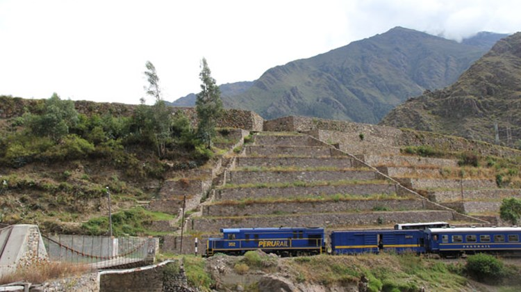 A train carrying passengers en route to Machu Picchu passes restored Inca terraces and a restored Inca bridge outside Ollantaytambo in the Sacred Valley.