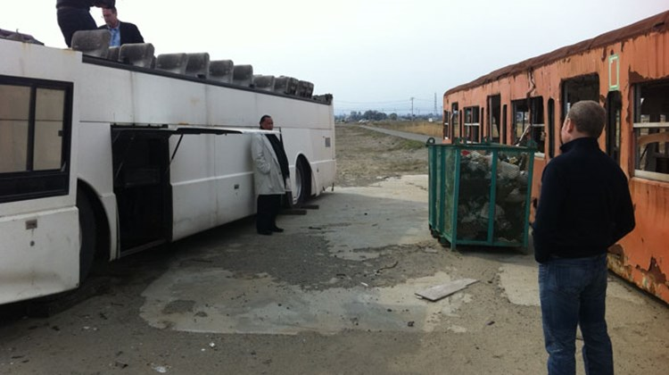 The large, flat area that was swept clean by the tsunami has become a staging area for damaged vehicles and other items awaiting dismantlement or removal. A train car (right) and tour bus are examined by CBS Travel Editor Peter Greenberg and cameraman Mark Wexler (on the bus), Taj Hotels and Resorts CEO Raymond Bickson (leaning against the bus) and Travel Corp CEO Bret Tollman. Photo by Arnie Weissmann