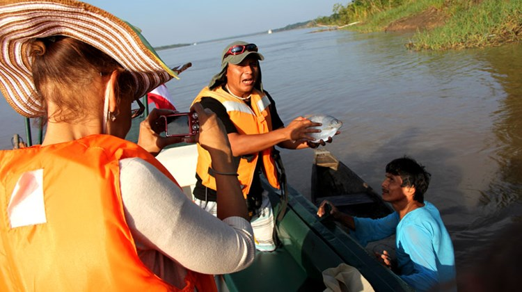 A G Adventures guide, holds a fruit-eating piranha caught by a local fisherman (right), while Vacation.com's Christine James snaps a photo.
