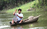 A fisherman paddles upstream on a tributary of the Amazon.