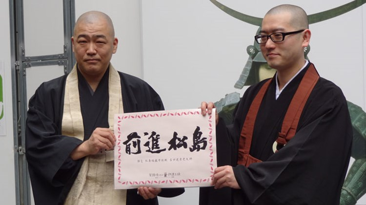 "Two Buddhist monks at the Zuiganji Temple in Matsushima, a coastal city south of Sendai severely damaged by the tsunami, hold a sign that says, ""Go forward Matsushima."""