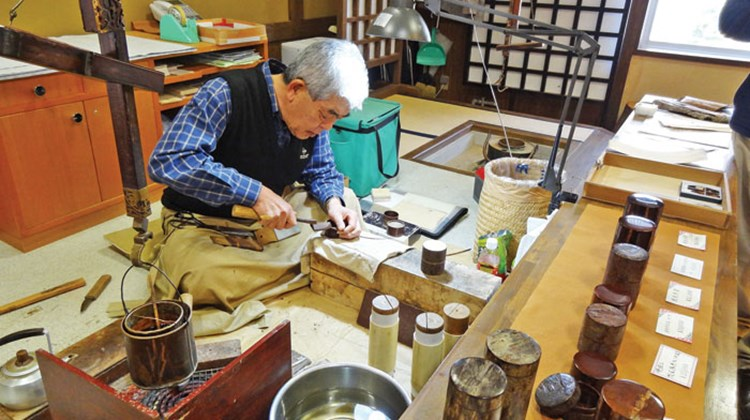 An artisan at a museum showcasing the history of cherry-tree bark crafts.