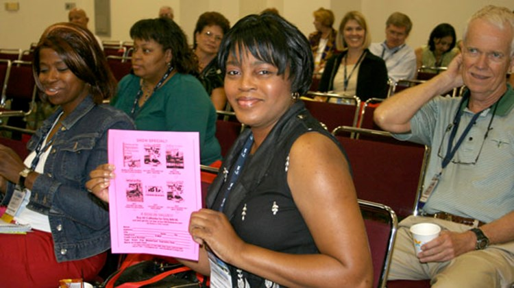 Kimberly Fountain, travel counselor, Splendid Destinations Travel, Sugar Land, Texas, showing off a coupon that entitles her to collect her prize of business books meant to assist home-based agents.