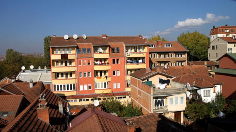 A brightly painted apartment house is the centerpiece of this city view in Pristina.