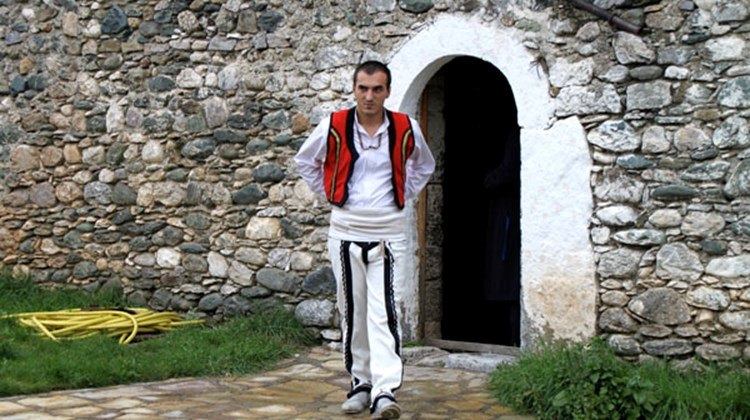 A host, in traditional dress, emerges from the Mazrekaj family kulla. The house was restored to receive tourists and locals for lunches and other events.