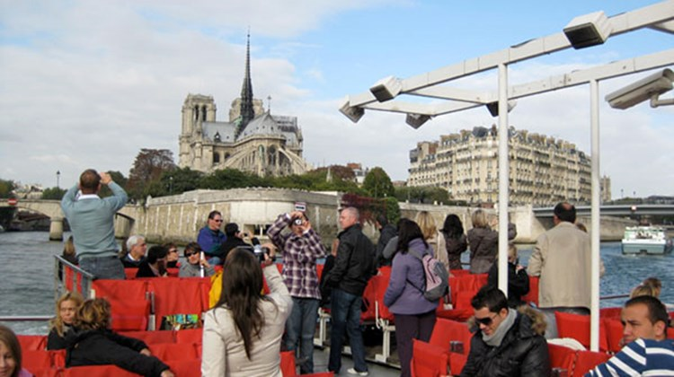 Tourists take in the view of Notre Dame cathedral from the Seine aboard a riverboat operated by Bateaux Parisiens.
