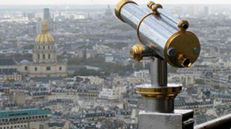 The steel and brass of an Eiffel Tower telescope find an echo in the stone and gold of the distant Sorbonne.