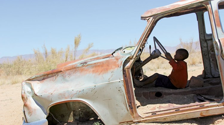 A local child plays among abandoned cars collected by a former Solitaire, Namibia, businessman.