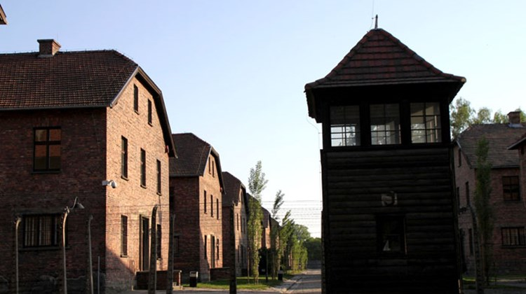 Barracks at the Auschwitz concentration camp outside of Krakow look innocuous here, but the guard tower and barbed wire in the foreground tell another story.