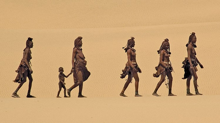 Himba women make their way through the Namibian desert with a child. Photo by Dana Allen/Wilderness Safaris