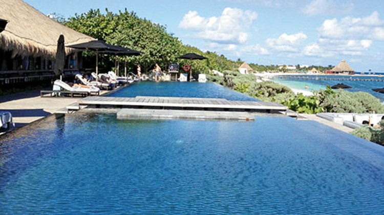 The adult side of Nizuc Resort & Spa features an infinity pool, flanked by sun lounges and the adjacent Punta Grill.