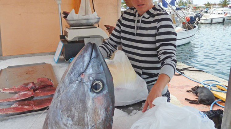 The fish vendors donate the head of the tuna, which will be used to make a fish soup for the galley crew.
